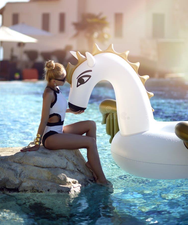 mujer que se relaja en hotel turístico de lujo de la piscina en el unicornio inflable grande que flota el flotador de Pegaso imagenes de archivo