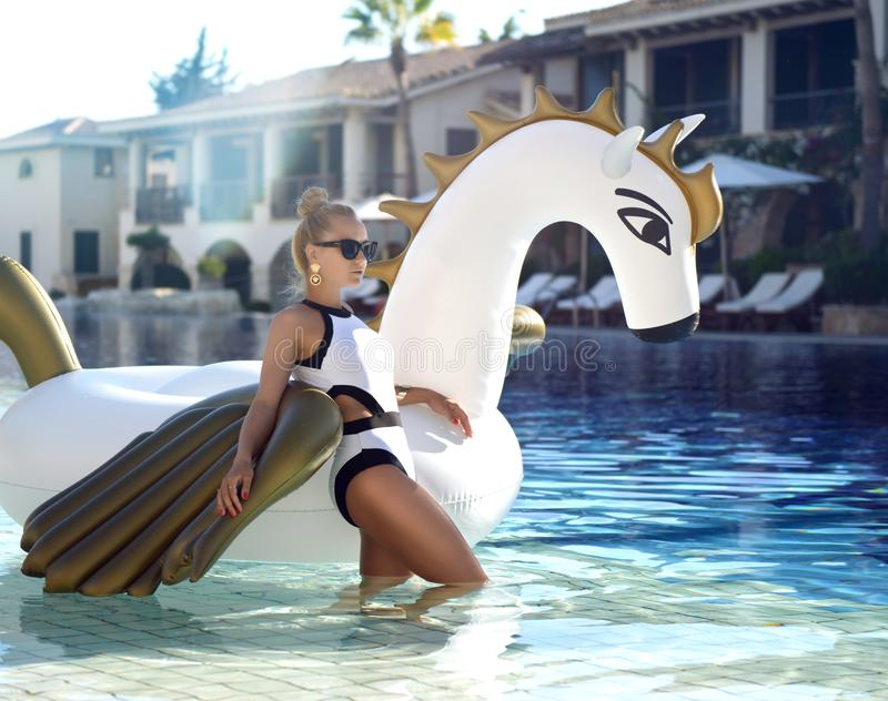mujer que se relaja en hotel turístico de lujo de la piscina en el unicornio inflable grande que flota el flotador de Pegaso foto de archivo libre de regalías