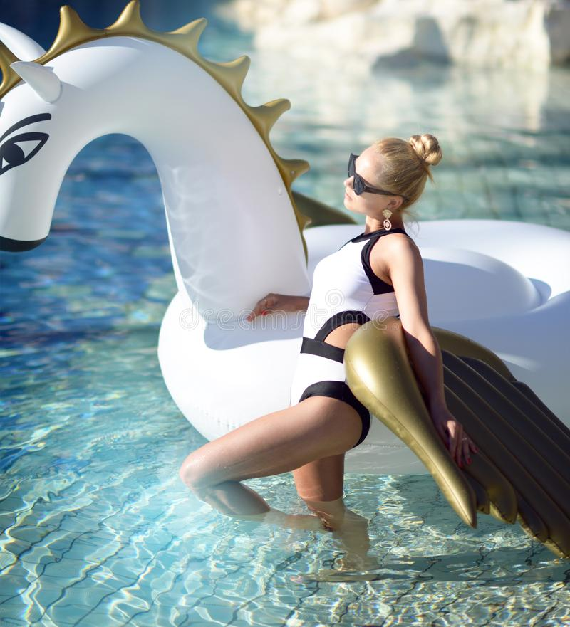 mujer que se relaja en hotel turístico de lujo de la piscina en el unicornio inflable grande que flota el flotador de Pegaso imagen de archivo libre de regalías
