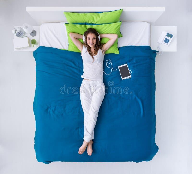 Mujer que se relaja en la cama imagen de archivo libre de regalías