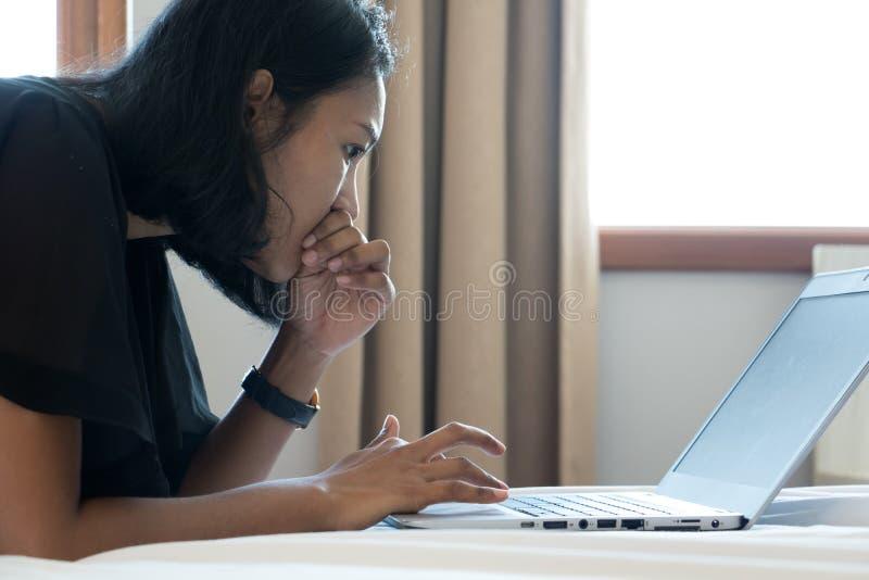 Mujer que se relaja en la cama blanca con el ordenador imagen de archivo