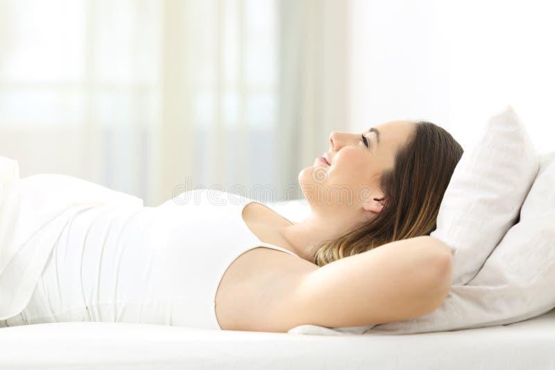 Mujer que se relaja en la cama en casa fotografía de archivo