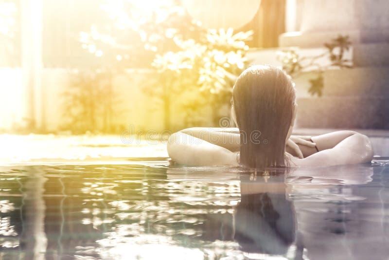 Mujer que se relaja en la piscina del balneario del hotel que mira la visión con el espacio de la luz del sol y de la copia foto de archivo libre de regalías