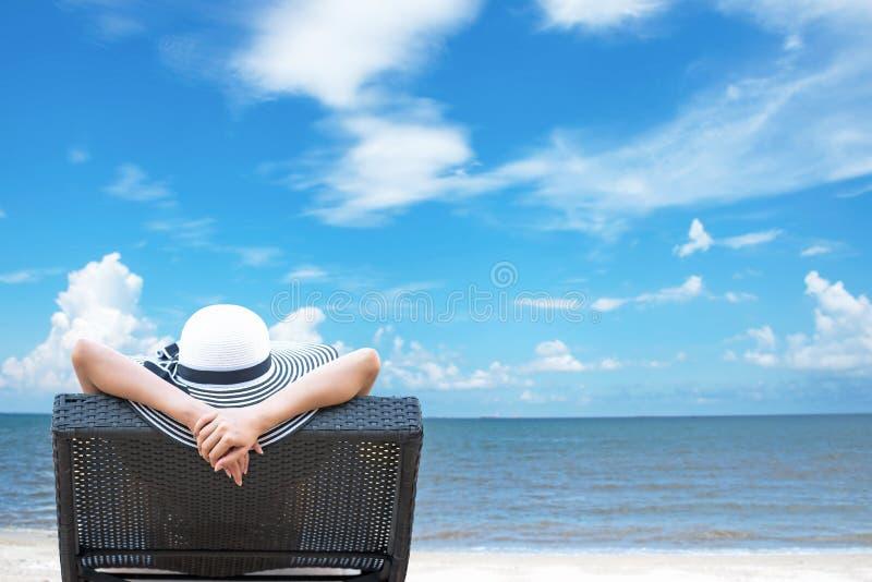 Mujer que se relaja en la playa de lujo, fondo del cielo azul fotografía de archivo libre de regalías