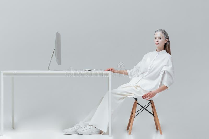 Mujer que se relaja en la tabla con el ordenador en la silla fotos de archivo libres de regalías