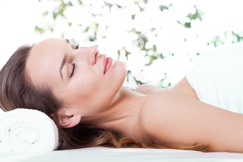 Mujer que se relaja en la tabla del masaje fotografía de archivo libre de regalías