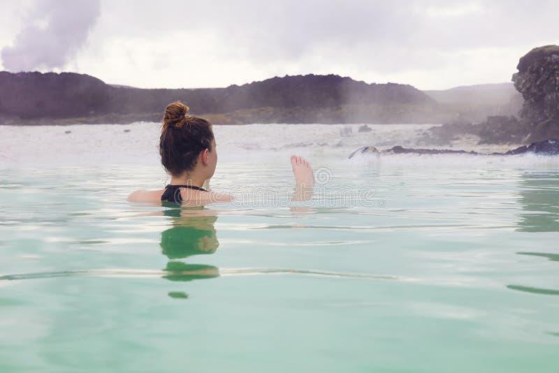 Mujer que se relaja en las aguas termales al aire libre en Islandia imágenes de archivo libres de regalías