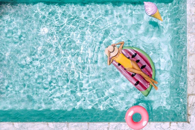 Mujer que se relaja en lilo inflable en piscina del hotel foto de archivo