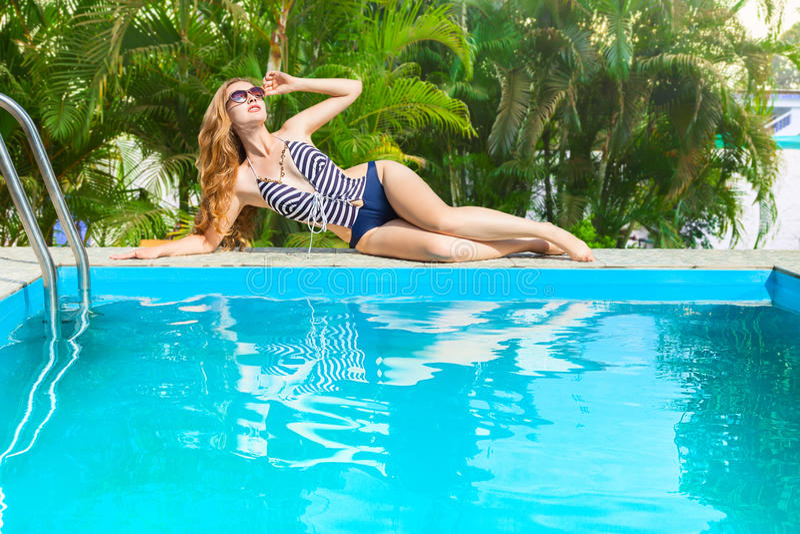Mujer que se relaja en piscina foto de archivo