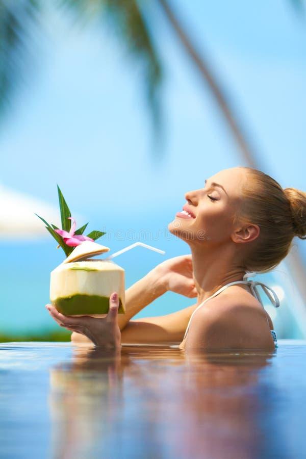 Mujer que se relaja en piscina con un cóctel imagen de archivo