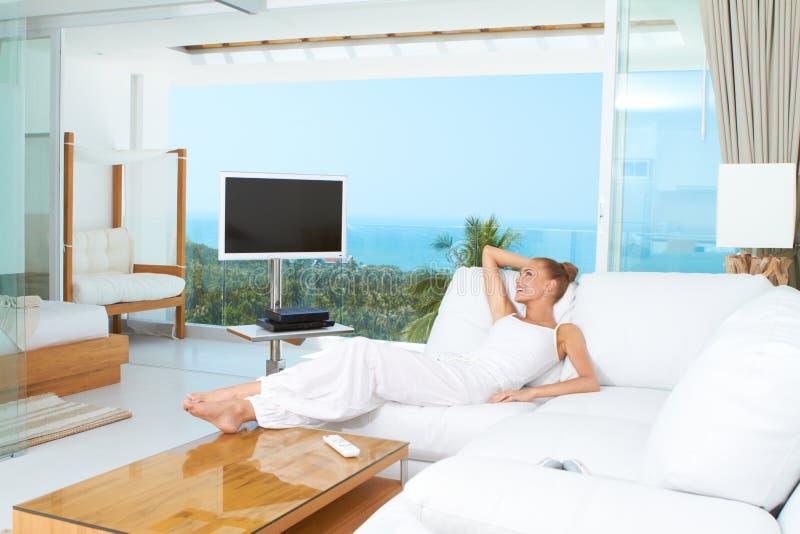 Mujer que se relaja en sala de estar brillante espaciosa imágenes de archivo libres de regalías