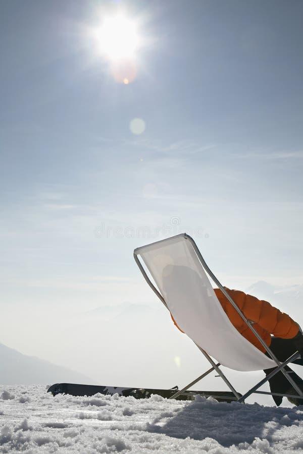 Mujer que se relaja en silla contra el cielo foto de archivo