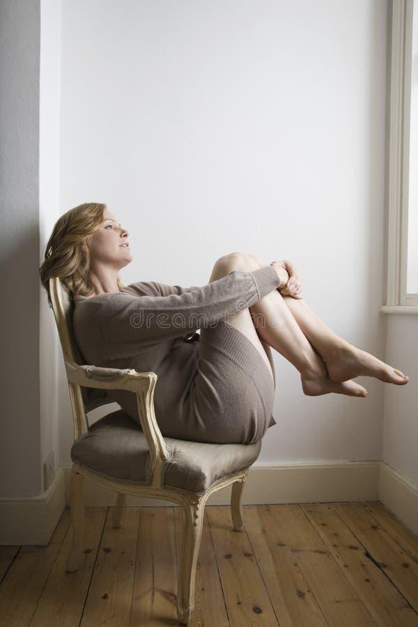 Mujer que se relaja en silla pasada de moda fotografía de archivo