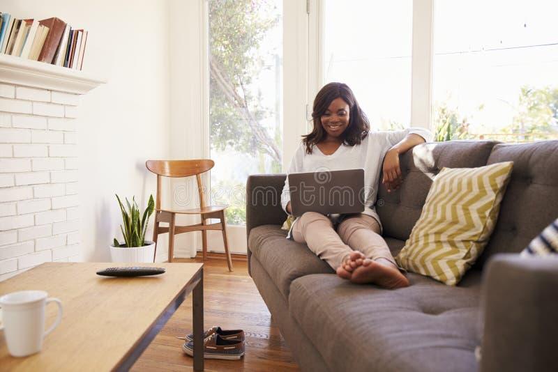 Mujer que se relaja en Sofa At Home Using Laptop imagenes de archivo