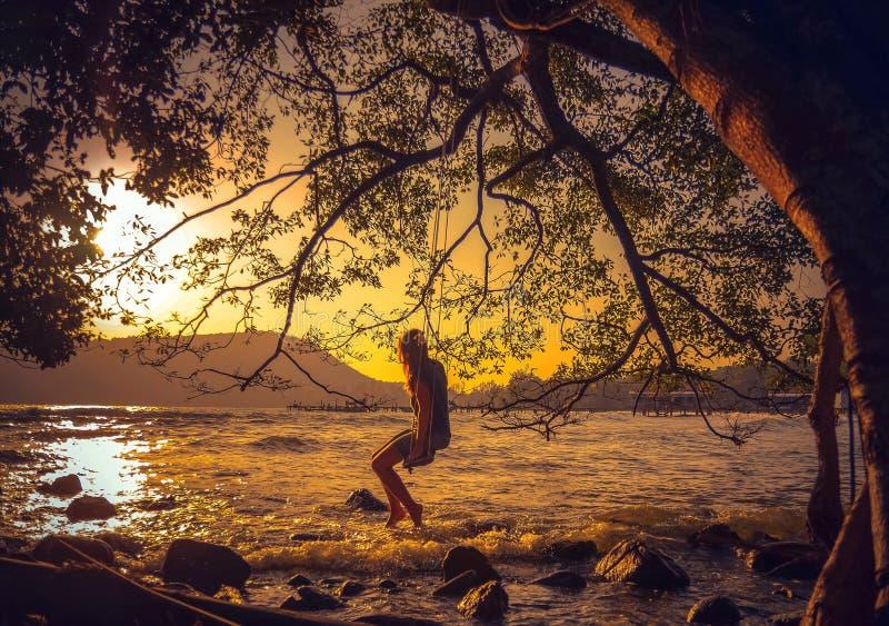 Mujer que se relaja en un oscilación en la playa fotos de archivo libres de regalías