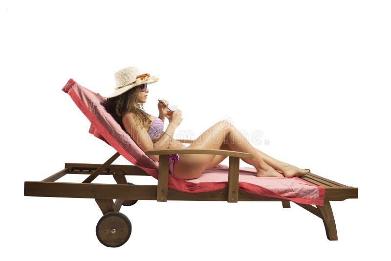 Mujer que se relaja en una playa imagen de archivo