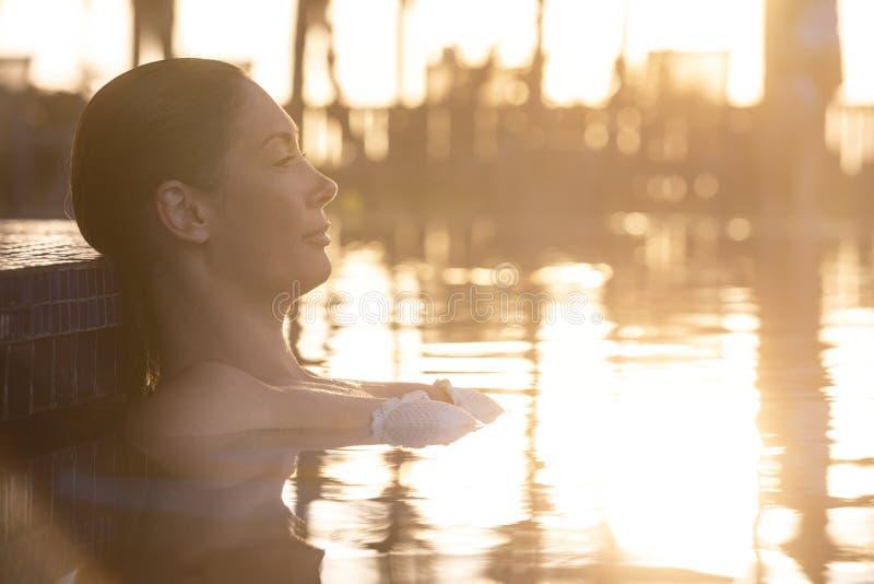 Mujer que se relaja por la piscina en la puesta del sol fotografía de archivo
