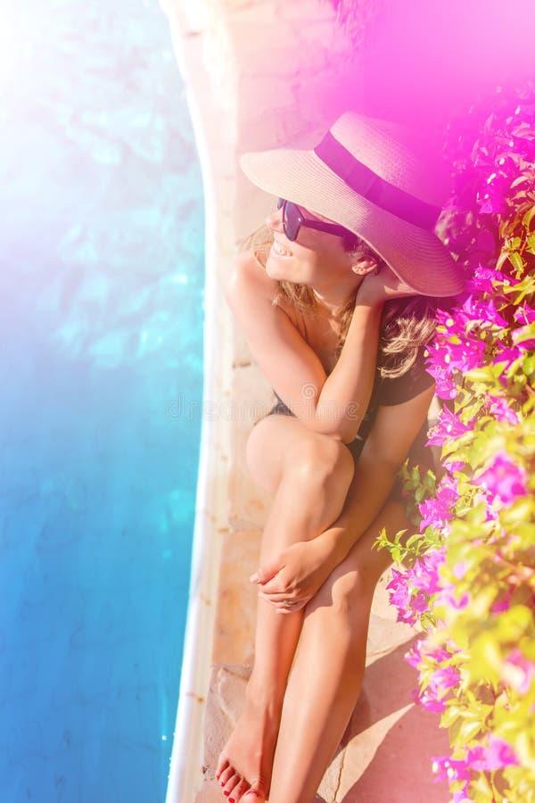 mujer que se relaja y que toma el sol en la piscina, las gafas de sol que llevan y el sombrero de paja del verano fotos de archivo libres de regalías