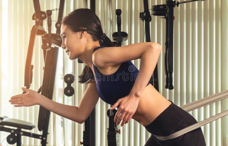 Mujer que se resuelve con el elástico de la resistencia en gimnasio fotos de archivo