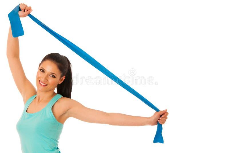 Mujer que se resuelve con la banda en el gimnasio de la aptitud aislado sobre blanco fotos de archivo