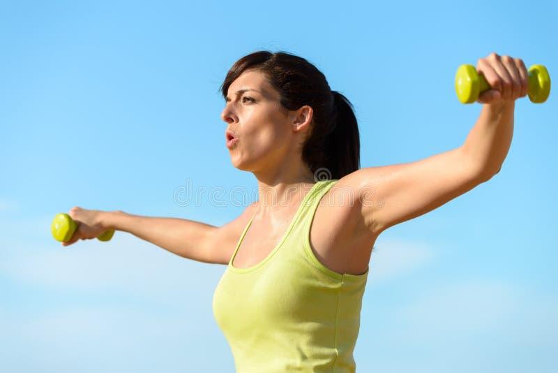Mujer que se resuelve con pesas de gimnasia fotografía de archivo
