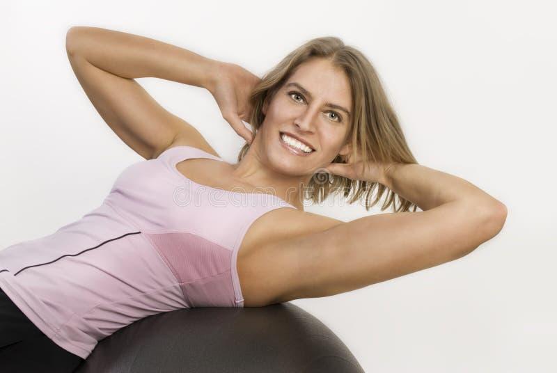 Mujer que se resuelve con una bola de la gimnasia imagen de archivo libre de regalías