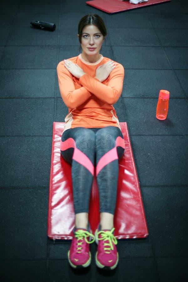 Mujer que se resuelve en el gimnasio imagenes de archivo