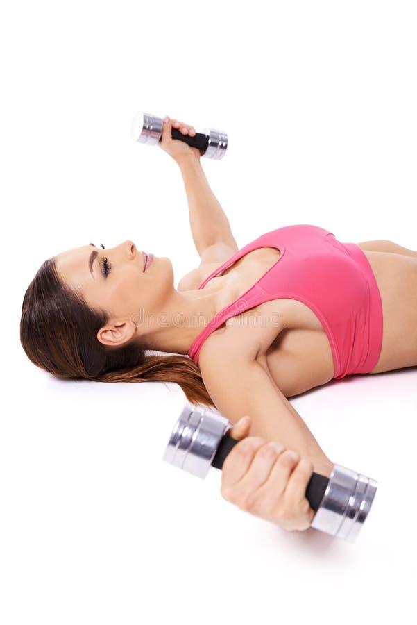 Mujer que se resuelve usando pesas de gimnasia fotos de archivo