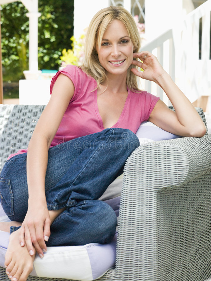 Mujer que se sienta al aire libre en la sonrisa del patio imagen de archivo libre de regalías