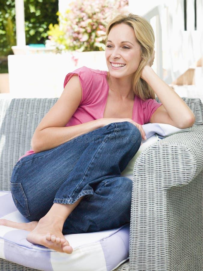 Mujer que se sienta al aire libre en la sonrisa del patio foto de archivo