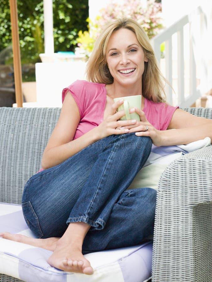 Mujer que se sienta al aire libre en patio con café foto de archivo libre de regalías