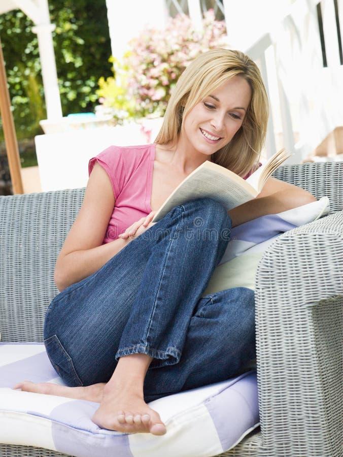 Mujer que se sienta al aire libre en patio con la sonrisa del libro fotografía de archivo libre de regalías