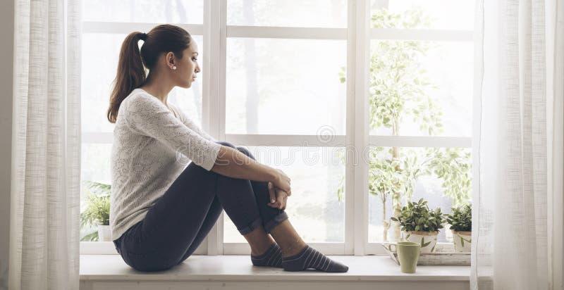 Mujer que se sienta al lado de una ventana y que mira lejos imagen de archivo