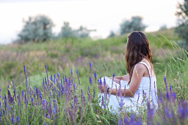 Mujer que se sienta cómodamente en la hierba imagenes de archivo