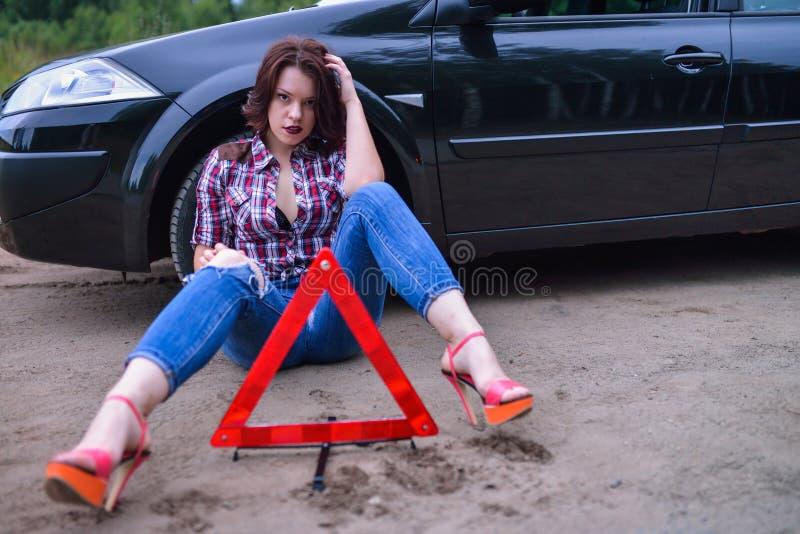 Mujer que se sienta cerca de su coche quebrado y triángulo amonestador fotos de archivo libres de regalías