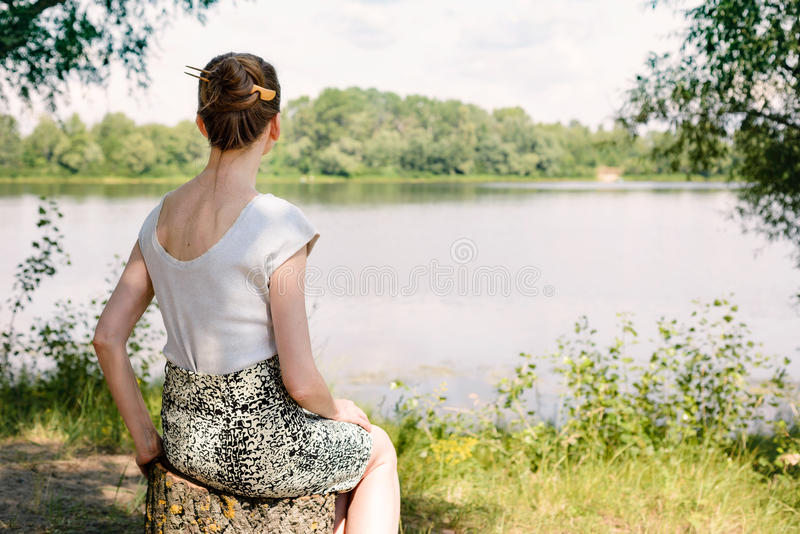 Mujer que se sienta cerca del río fotos de archivo libres de regalías