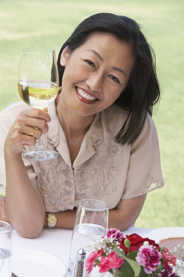 Mujer que se sienta con la copa en la tabla al aire libre imagen de archivo
