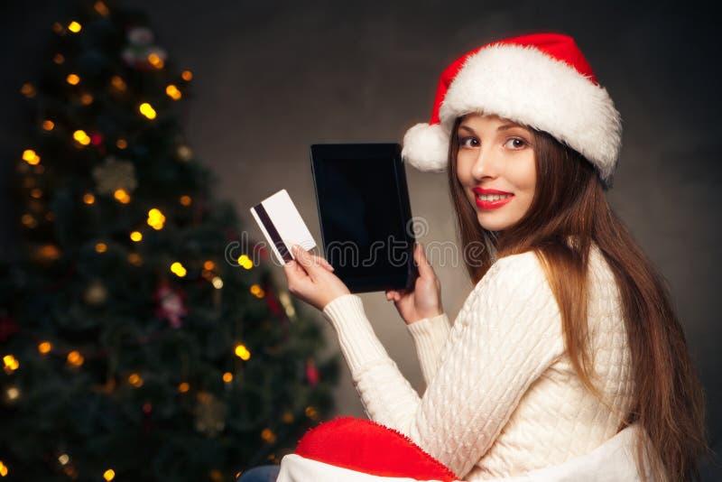 Mujer que se sienta con la tableta y la tarjeta sobre el árbol de navidad imagen de archivo libre de regalías
