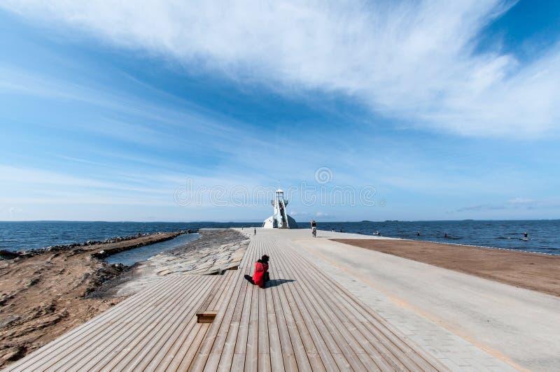 Mujer que se sienta delante de un faro en Oulu, Finlandia imagen de archivo