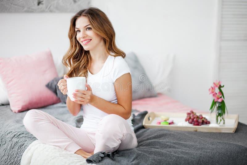 Mujer que se sienta en cama foto de archivo