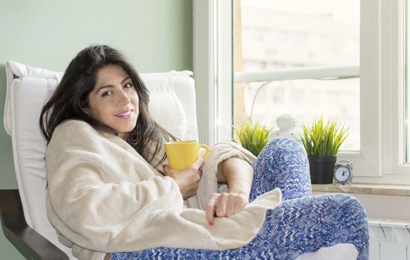 Mujer que se sienta en casa, envuelto en una manta, té de consumición imagenes de archivo