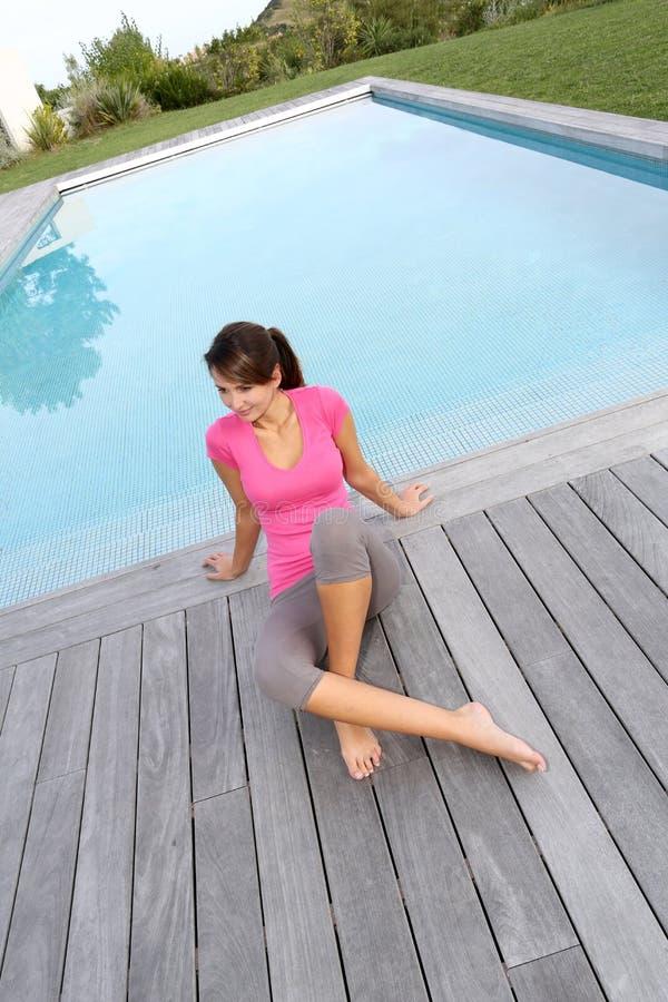 Mujer que se sienta en cubierta de la piscina