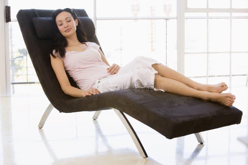 Mujer que se sienta en dormir de la silla imágenes de archivo libres de regalías