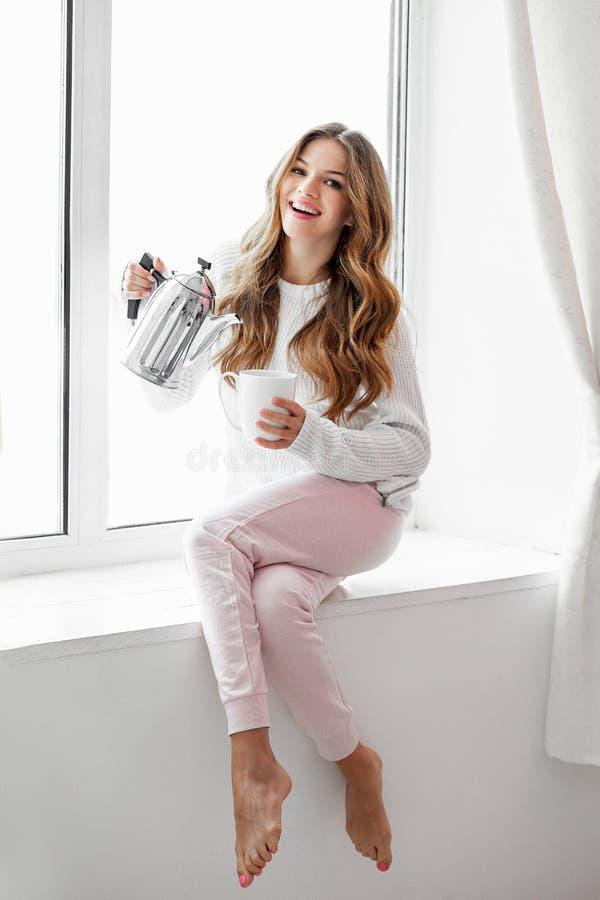 Mujer que se sienta en el alféizar y el té o el café de colada de la caldera imagen de archivo libre de regalías