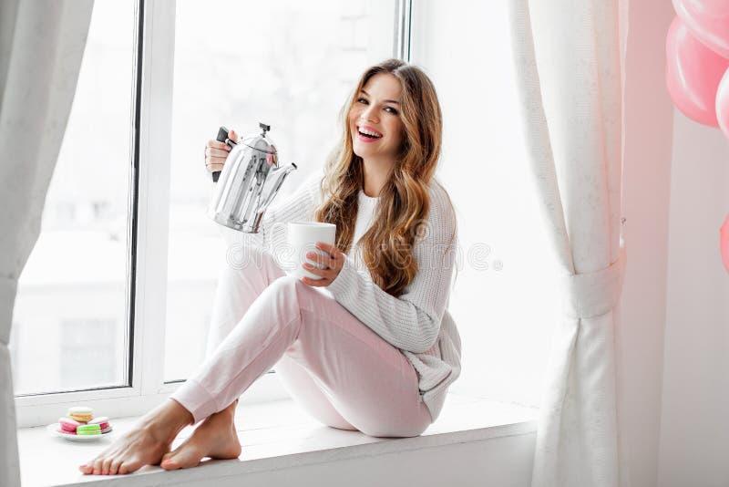 Mujer que se sienta en el alféizar y el té o el café de colada de la caldera imagen de archivo