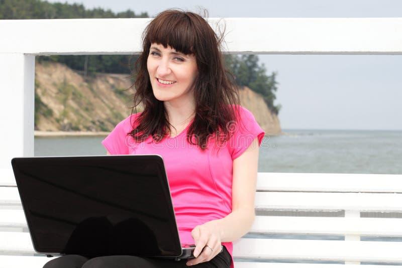 Mujer que se sienta en el banco con su computadora portátil imagenes de archivo
