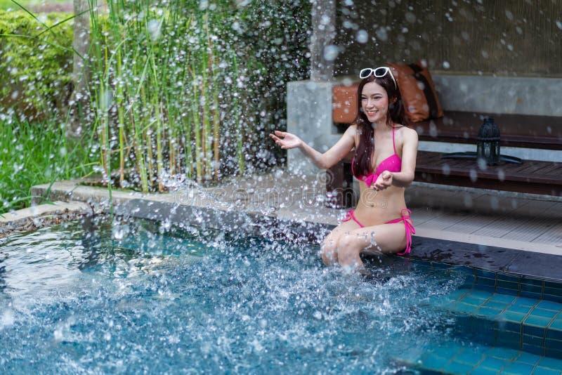 Mujer que se sienta en el borde de la piscina y que juega el chapoteo del agua fotos de archivo libres de regalías