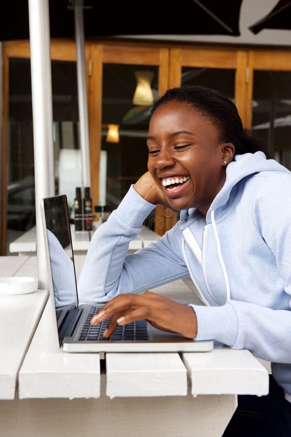 Mujer que se sienta en el café usando el ordenador portátil foto de archivo