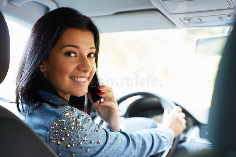 Mujer que se sienta en el coche y la llamada fotografía de archivo libre de regalías