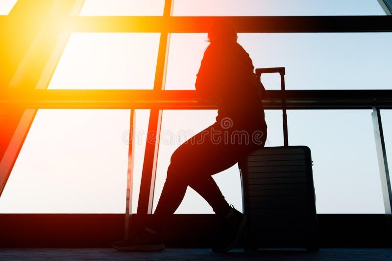 Mujer que se sienta en el equipaje del viaje que mira fuera de hogar perdido de la ventana imagen de archivo libre de regalías